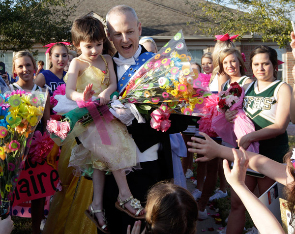 Five-year-old Claire Lankford waves to friends as she is carried by her father Kevin down the red carpet in front of their League City home as hundreds of people cheer during a special Princess Claire Day celebration on Wednesday evening February 19, 2014.